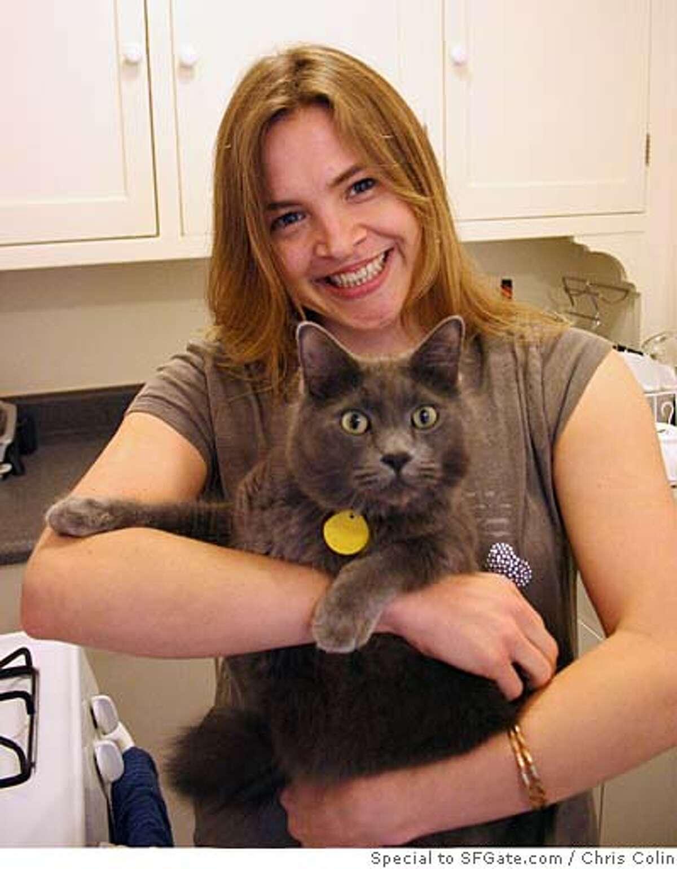 Monika Thomas in one of many strangers' kitchens, holding one of many strangers' cats. Photo by Chris Colin.