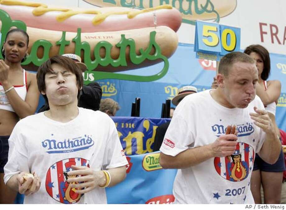 Takeru Kobayashi, left, and Joey Chestnut, right, eat hot dogs during Nathan's Famous Hot Dog Eating Competition in New York, Wednesday, July 4, 2007. In a gut-busting showdown that combined drama, daring and indigestion, Joey Chestnut emerged this afternoon as the world's hot dog eating champion by gobbling down a record 66 franks. The Californian knocked off six-time titlist Takeru Kobayashi in a rousing yet repulsive triumph in Coney Island. (AP Photo/Seth Wenig) Photo: Seth Wenig