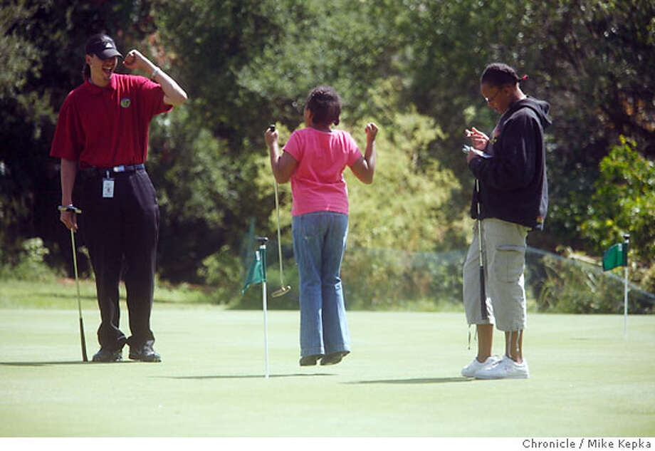 family0500000079.JPG  Golf Specialist for the City of Oakland, Preston Pinkney ecourages Heather Davis , 11, after she put a putt in the hole with friend Taylor Reynolds, 11, watching (rt). Oakland�s Parks and Recreation Department offers free golf instruction in two-week sessions for beginners, intermediate players at Lake Chabot�s nine-hole three-par course. Most of the participants, aged nine to 17, are from the inner city and have little or no experience with golf. Residents and non-residents are welcome. 6/28/07. Mike Kepka / The Chronicle Preston Pinkney Heather Davis Taylor Reynolds(cq) Photo: Mike Kepka