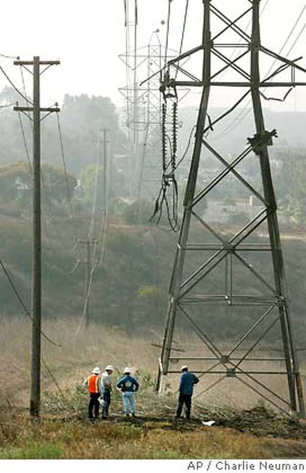 A San Diego Gas and Electric crew stands below damaged electrical wires at The Crossings at Carlsbad golf course that was hit by a private plane, which crashed in flames, killing two people, as it took off from from McClellan-Palomar Airport in Carlsbad, Calif., Tuesday, July 3, 2007. The four-seat airplane was taking off in light fog when it went down around 6 a.m. on a municipal golf course less than a mile west of the airport, police and fire officials said. (AP Photo/San Diego Union-Tribune, Charlie Neuman) ** SAN DIEGO COUNTY OUT, NO SALES, COMMERCIAL, INTERNET OUT, FOREIGN OUT, MANDATORY CREDIT ** SAN DIEGO COUNTY OUT, NO SALES, COMMERCIAL, INTERNET OUT, FOREIGN OUT, MANDATORY CREDIT Photo: Charlie Neuman
