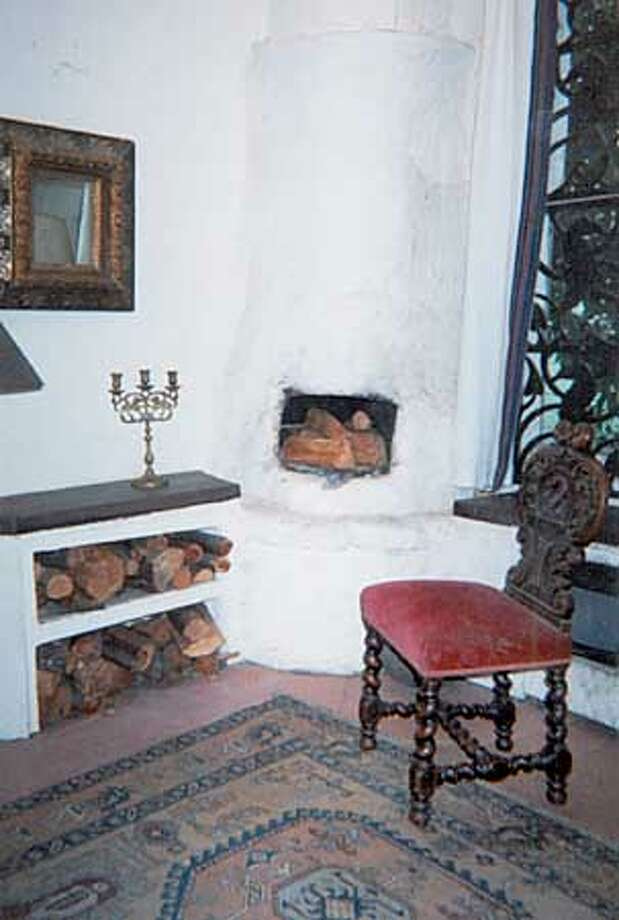 THE KIVA-LIKE FIREPLACE ZEB CONLEY MADE FOR THE CORNER OF HIS 450 SQUARE FOOT RENTAL