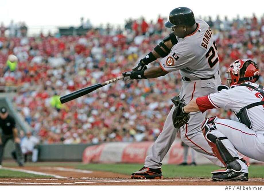 San Francisco Giants' Barry Bonds hits a two-run home run off Cincinnati Reds pitcher Aaron Harang in the first inning of a baseball game, Tuesday, July 3, 2007, in Cincinnati. Reds catcher David Ross is at right. The home run was the 751st of Bond's career. (AP Photo/Al Behrman) Photo: Al Behrman