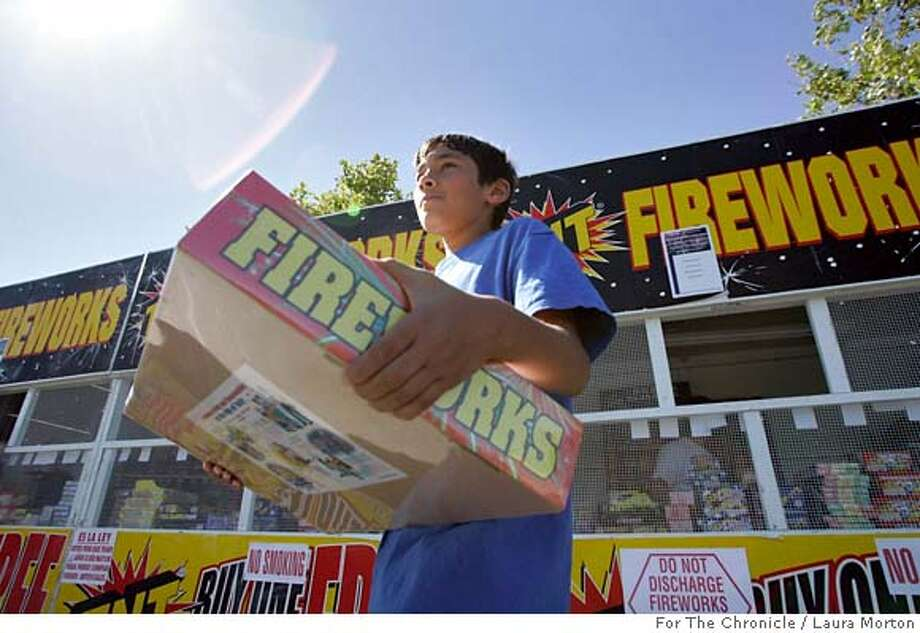 fireworks_0031_LKM.jpg Phillip Bannister, age 12, walks away with fireworks he and his dad purchased at a stand in Dublin, CA. The stand, fundraising for Valley Christian Center, is one of many in Dublin, all of which are fundraisers for non-profits. Bannister said they planned to use the fireworks during a family get together. (Laura Morton/Special to the Chronicle) *** Phillip Bannister Photo: Laura Morton