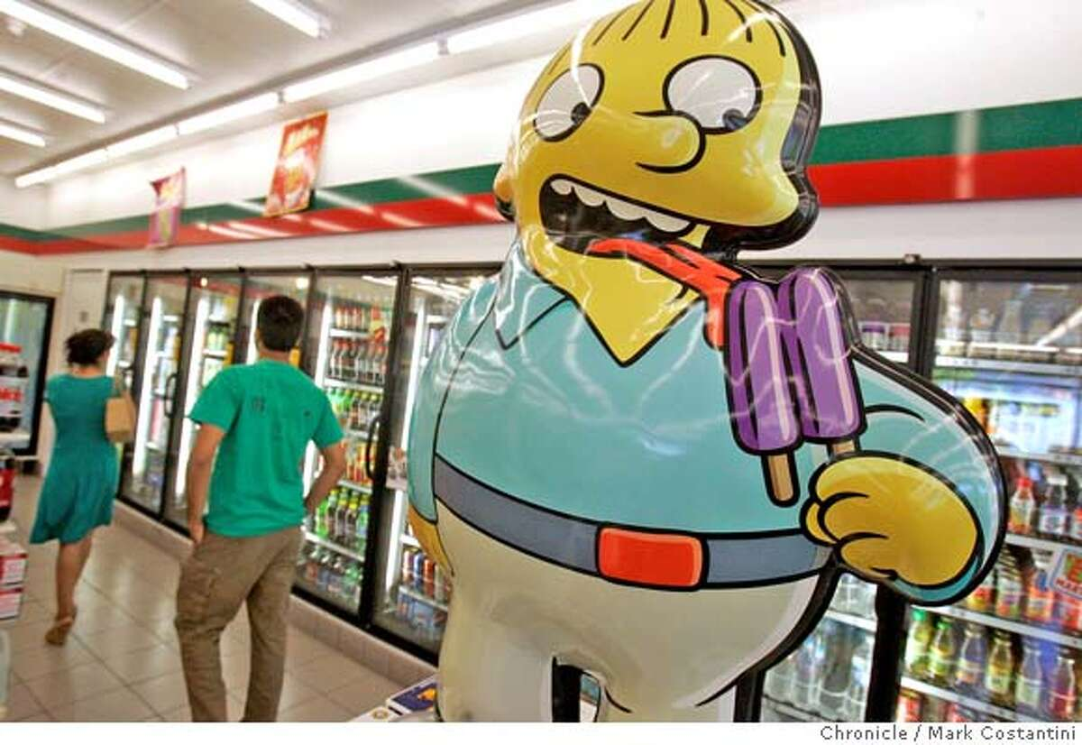 Shoppers look through drink section of store. 7-Eleven is changing several of their stores to Kwik-E-Mart franchises, including this one in Mountain View. There's a promotional tie to the new Simpsons movie. PHOTO: Mark Costantini / The Chronicle MANDATORY CREDIT FOR PHOTOGRAPHER AND SAN FRANCISCO CHRONICLE/NO SALES-MAGS OUT