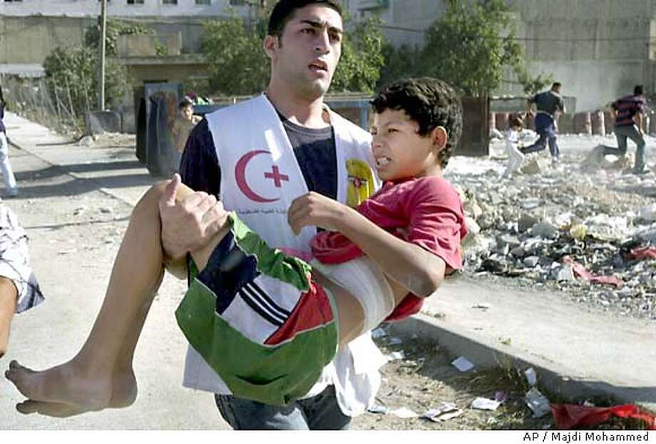 A injured Palestinian boy is carried to an ambulance after being during clashes with Israeli soldiers at a refugee camp in the West Bank town of Nablus, Thursday, Oct. 9, 2003. (AP Photo/Majdi Mohammed) Photo: MAJDI MOHAMMED