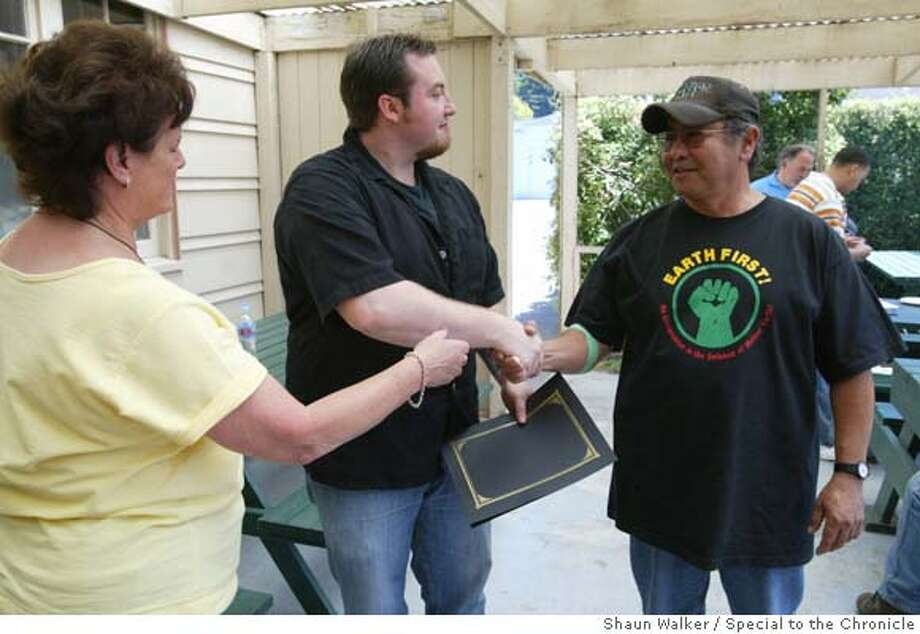 Humboldt State Univeristy Veterans Upward Bound director Cai Williams, left, gives Jarad Chase-Dunn his certificate as he shakes academic advisor David Shaw's hand during an informal graduation party in Arcata on Wednesday.  special to the Chronicle Shaun Walker Photo: Shaun Walker