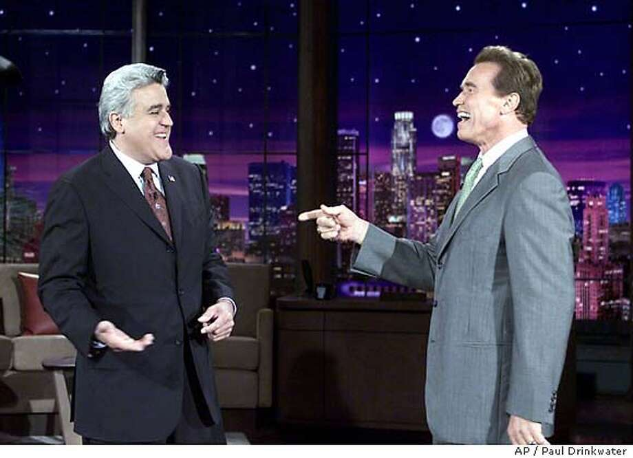"Governor-elect Arnold Schwarzenegger, right, points to Jay Leno after he walks on stage at the end of Leno's monologue during taping of ""The Tonight Show with Jay Leno"" Wednesday, Oct. 8, 2003, in Burbank, Calif. Schwarzenegger said he was ""in the neighborhood"" and wanted to thank Leno for introducing him at his victory speech last night. This marks the first time Schwarzenegger has been on the show since August 6 when he surprised everyone by announcing his candidacy for Governor of California. (AP Photo/Paul Drinkwater/NBC,HO) Photo: PAUL DRINKWATER"