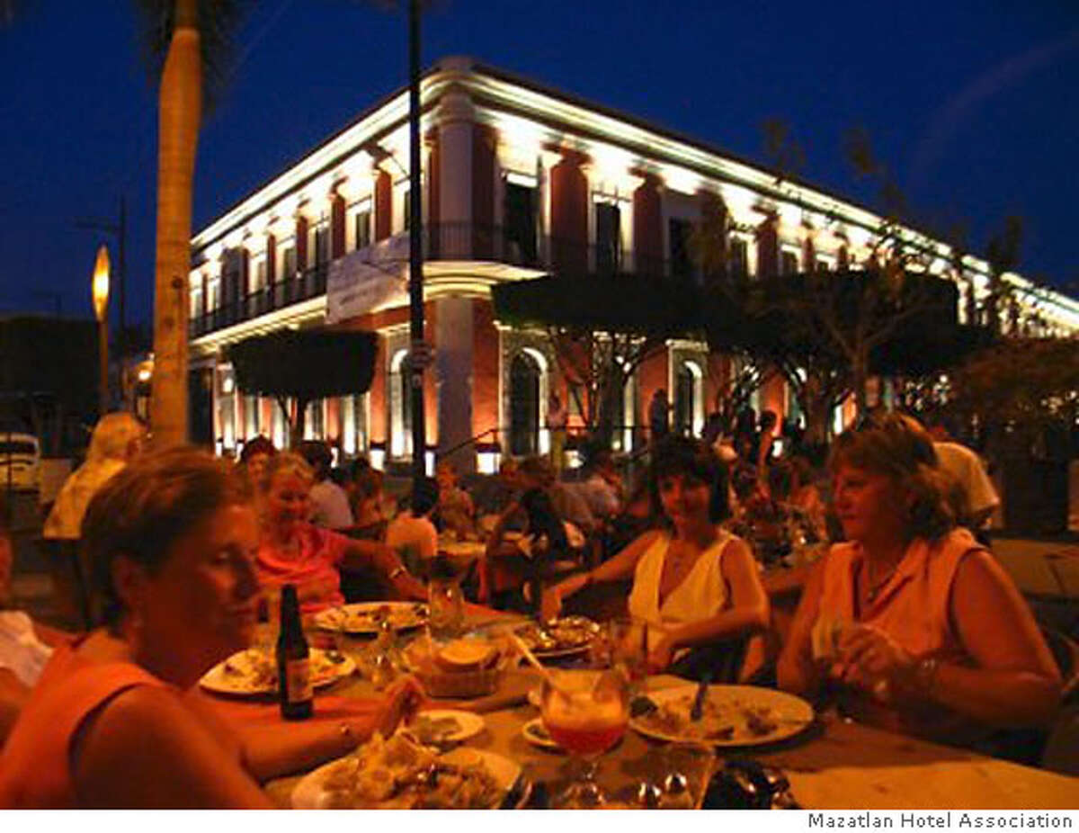 TRAVEL MAZATLAN -- Plazuela Machado is ringed by outdoor cafes; the restored Angela Peralta Theater building rises in the background. with outdoor diners in the evening tables Credit: Mazatlan Hotel Association