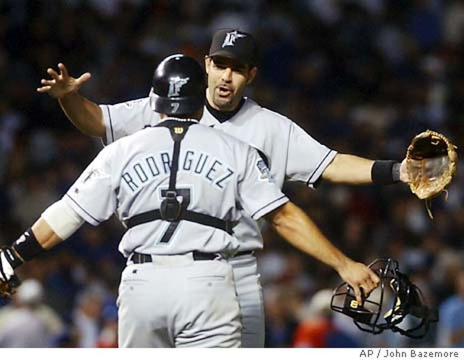 Florida Marlins' Mike Lowell and Ivan Rodriguez celebrates thier 9-8 win over the Chicago Cubs in Game 1 of the National League championship series Tuesday, Oct. 7, 2003, at Wrigley Field in Chicago. Lowell hit the game-winning hit, a solo homer in the 11th inning. (AP Photo/John Bazemore) Photo: JOHN BAZEMORE