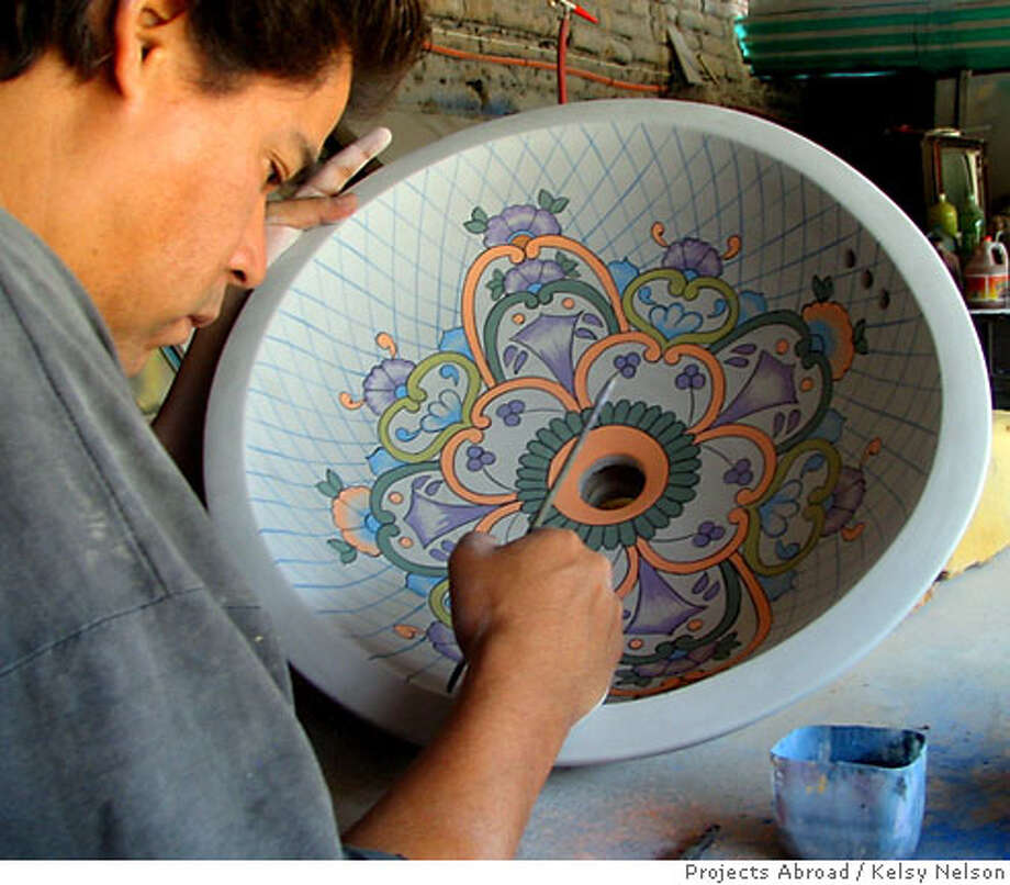 TRAVEL VOLUNTEER -- Local artisan Juan Carlos Ramirez Guzman paints a sink. Kelsy Nelson / Projects Abroad  Ran on: 07-01-2007  Arts and crafts, like this sink being painted by a local artisan, are part of Projects Abroad volunteer programs in Mexico. Photo: Kelsy Nelson