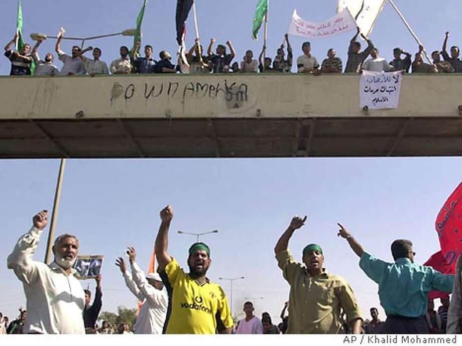Shiite Muslims protest in southwest Baghdad, where some 600 demonstrators at a Shiite Muslim mosque confronted U.S. soldiers, Tuesday Oct 7, 2003. The protesters claimed the Americans had illegally detained their imam, Sheikh Mohammed al-Sudani. (AP Photo/Khalid Mohammed) Photo: KHALID MOHAMMED