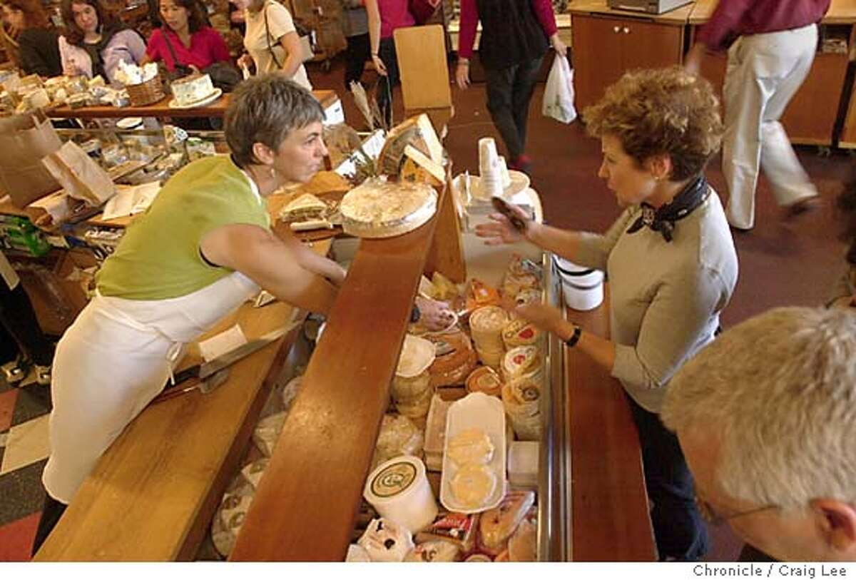 Cheese Board, the oldest food collective in Northern California. It's a pizza shop, as well as a place to get nice quality cheeses and bread. It is located at 1504 Shattuck in Berkeley. Photo of Ursula Schulz behind the counter helping customers with cheese. Event on 9/26/03 in Berkeley. CRAIG LEE / The Chronicle