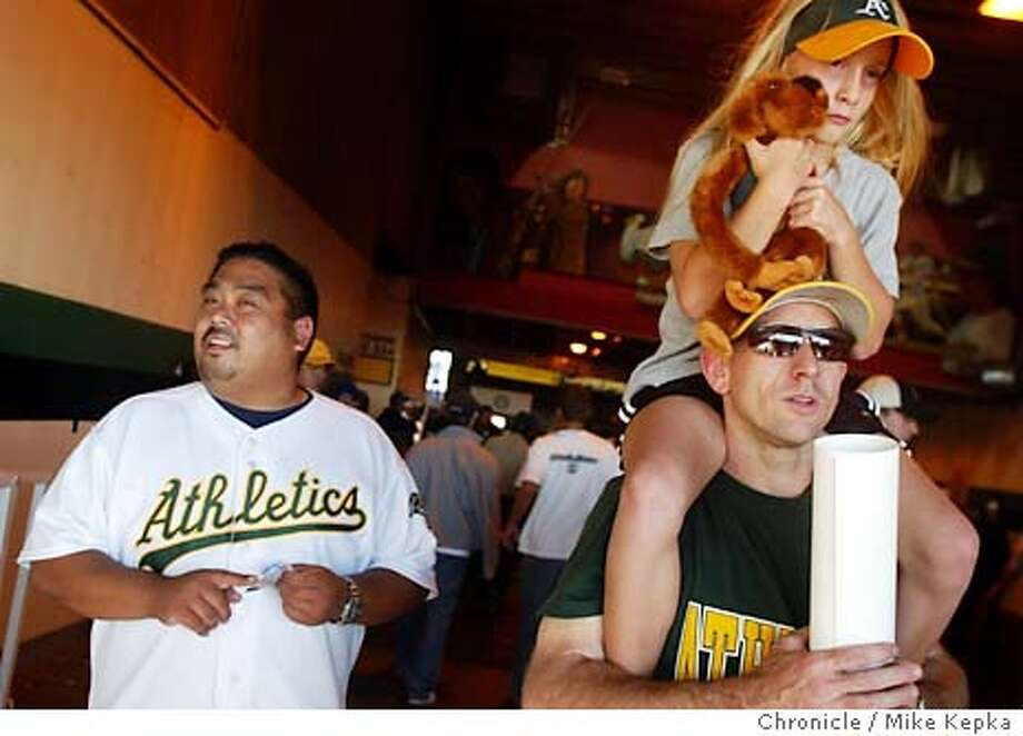 athletics_076_MK.jpg  Oakland Athletics fan Rudy Guzman, of San Leandro, left, and Matt Cruse with his daugter Catherine Cruz, 9, of Graeagle, Ca., watch the early innings of play. The Oakland Athletics play the Boston Red Sox in Game 5 of the American League Division Series at Oakland Coliseum 10/6/03 in Oakland. Mike Kepka / The Chronicle Photo: Mike Kepka