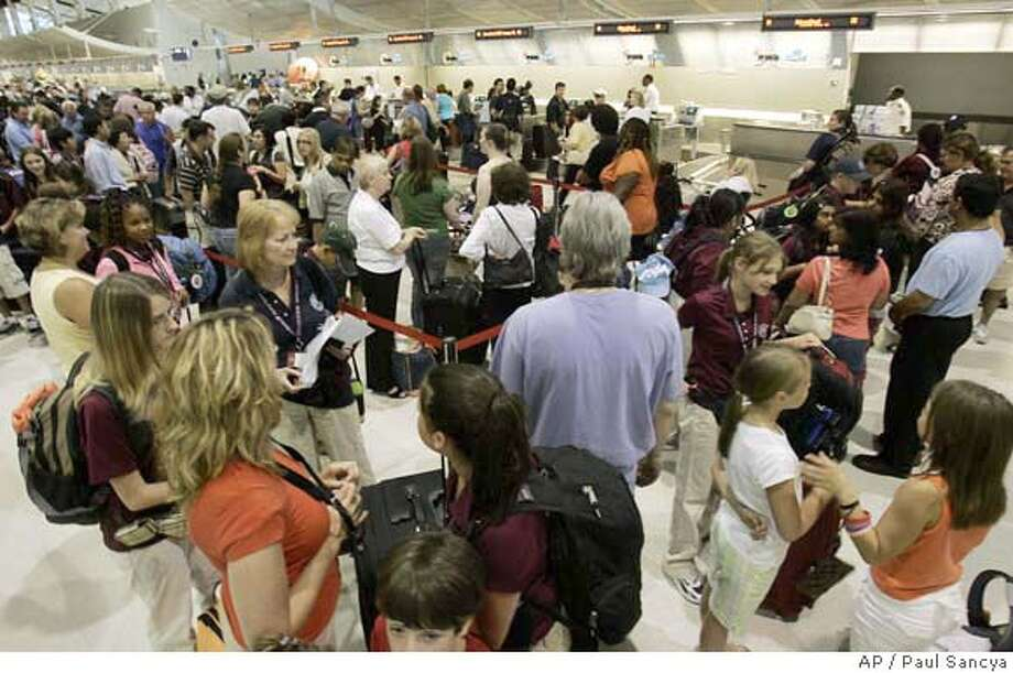 Passengers wait in line to check in for Northwest Airlines flights at Detroit Metropolitan Airport in Romulus, Mich., Wednesday, June 27, 2007. Acrimony between Northwest Airlines pilots and management may be to blame for hundreds of canceled flights in recent days, but analysts say the airline needs to resolve the situation quickly to avoid further damaging its reputation. (AP Photo/Paul Sancya) Photo: Paul Sancya