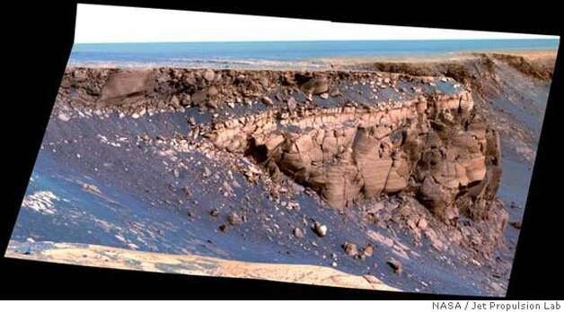 "This image captured by NASA's Mars Exploration Rover Opportunity shows ""Cape St. Vincent,"" one of the many promontories that jut out from the walls of Victoria Crater, Mars. The material at the top of the promontory consists of loose, jumbled rock, then a bit further down into the crater, abruptly transitions to solid bedrock. This transition point is marked by a bright band of rock, visible around the entire crater. Scientists say this bright band represents what used to be the surface of Mars just before an impact formed Victoria Crater. After Opportunity begins to descend into the crater in early July 2007, it will examine the band carefully at an accessible location with a gentle slope. These investigations might help determine if the band's brighter appearance is the result of ancient interactions with the Martian atmosphere. This image was taken by Opportunity's panoramic camera on sol 1167 (May 6, 2007). It is presented in false color to accentuate differences in surface materials. Image credit: NASA/JPL/Cornell Photo: NASA/Jet Propulsion Lab./Cornell"