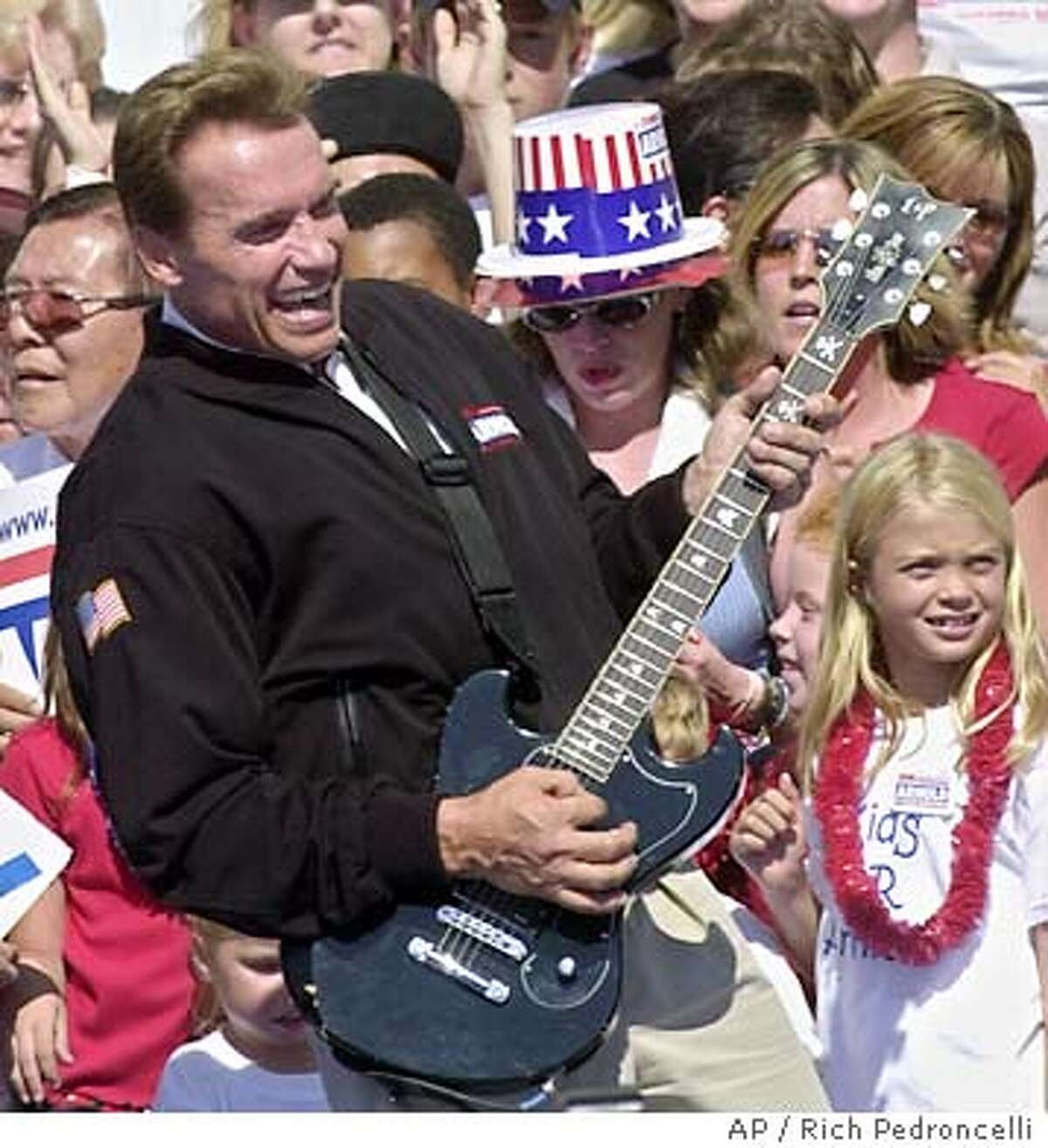 Republican gubernatorial candidate Arnold Schwarzenegger, playfullly strums a guiter to the Twisted Sister song,