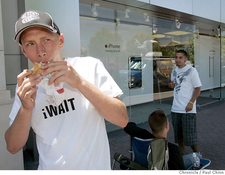 Chris Lionel eats a hamburger while he and three high school buddies from Benicia wait in line to buy the highly anticipated iPhone in Walnut Creek, Calif. on Wednesday, June 27, 2007 when it goes on sale Friday at the Apple Store. The group arrived at 5 a.m. and hope to sell the first two spots in line and then purchase up to five iPhones to sell on eBay and earn money for college.  PAUL CHINN/The Chronicle  **Chris Lionel Photo: PAUL CHINN