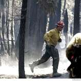 TAHOEFIRE_44702.JPG  US Forest Service firefighter Tim Memmer from Smith River Ca station runs from a tree that snapped just seconds before it fell. It was a hazard after yesterday fire that threatened the Garden mountain neighborhood Tuesday. South Lake Tahoe's Angora Fire continues to burn, but at a slower pace than yesterday inferno that threatened 500 homes in the Garden Mountain area of South Lake Tahoe. To date the fire has consumed 175 to 200 homes in Meyers and South Lake Tahoe. An additional 3,000 acres of forest have been lost or damaged. The wind-driven blaze is laying down for the moment as winds have dissipated since dust Tuesday, 1,888 plus firefighters continue to try to put a ring around the blaze that is 44% contained. (June 27) (cq) SUBJECT) Lance Iversen / The Chronicle Photo taken on 6/27/07,in SOUTH LAKE TAHOE, CA. Ran on: 06-28-2007  Tim Memmer, a Forest Service firefighter, runs from a tree just seconds before it snapped and fell.  Ran on: 06-28-2007  Tim Memmer, a Forest Service firefighter, runs from a tree just seconds before it snapped and fell.