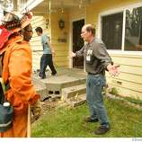 Mark Anthenien, right questions the fire fighters as the flames creep through the forest towards his home on Gardner Mountian Tuesday June 26, 2007, in South Lake Tahoe, Ca. (Lacy Atkins /San Francisco Chronicle)  *Mark Anthenien Ran on: 06-28-2007  Tim Memmer, a Forest Service firefighter, runs from a tree just seconds before it snapped and fell.  Ran on: 06-28-2007  Tim Memmer, a Forest Service firefighter, runs from a tree just seconds before it snapped and fell.