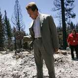 California Governor Arnold Schwarzenegger curls a dumbbell that was found in the remains of a home that was burned down on Sunday in the Angora wildfire near South Lake Tahoe, California June 27, 2007. REUTERS/Jeff Chiu/Pool (UNITED STATES)