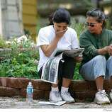 Lydia Zuniga reads the latest news with her sister Juana Anthenien, Wednesday June 27, 2007 outside the Anthenien home which was saved from the fire Tuesday, along Gardner Mountain, in South Lake Tahoe, Ca. (Lacy Atkins /San Francisco Chronicle)  *Lydia Zuniga ** Juana Anthenien