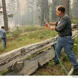 Mark Anthenien, right feed garden hose to his son Greg to go wet down the fireline between the blame and their home on Gardner Mountian Tuesday June 26, 2007, in South Lake Tahoe, Ca. (Lacy Atkins /San Francisco Chronicle)  *Mark Anthenien