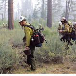 Firefighters from the Klamath Hotshots in Yreka, Calif., form a grid looking for hotspots of the Angora fire near Highway 89, Wednesday, June 27, 2007, in South Lake Tahoe, Calif. (AP Photo/Ben Margot)