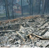 The remains of a home that was burned down on Sunday in the Angora wildfire are shown in front of a home that survived near South Lake Tahoe, Calif., Wednesday, June 27, 2007. (AP Photo/Jeff Chiu)