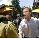 California Gov. Arnold Schwarzenegger, center, greets firefighters after speaking at a news conference about the Angora wildfire near South Lake Tahoe, Calif., on Wednesday, June 27, 2007. (AP Photo/Jeff Chiu)