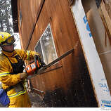 TAHOEFIRE_44334.JPG  Firefighter Darren Zimmerman from South Placer Fire Dist cuts into the side of a home looking for hot spots on Mt Rainier Drive in Meyers that was saved. South Lake Tahoe's Angora Fire continues to burn, but at a slow pace do to the lack of wind. The inferno that consumed 173 buildings, most of which are homes in Meyers California also consumed an additional 2,500 acres of forest in both Meyers and South Lake Tahoe. 450 plus firefighters continue to try to put a ring around the blaze that is 60% contained but threatening another 500 homes close to South Lake Tahoe High school. (June 26) (cq) SUBJECT) Lance Iversen / The Chronicle Photo taken on 6/26/07,in MEYERS, CA.