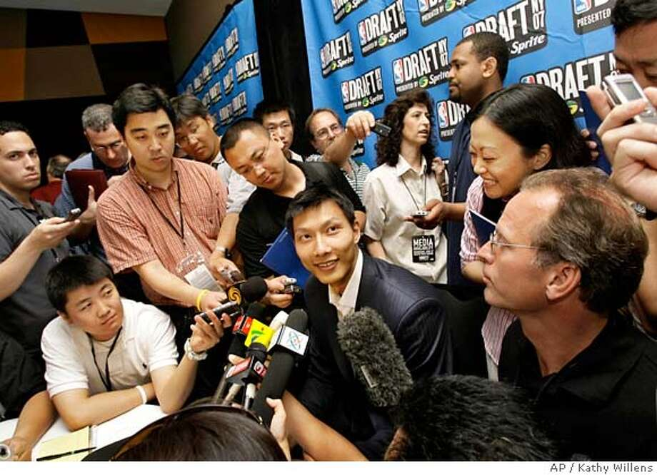 Chinese basektball star Yi Jinalian, in the top ten for Thursday's NBA Draft, endures a throng of reporters with a smile during a news conference in New York, Wednesday, June 27, 2007. The NBA Draft will be held Thursday at Madison Square Garden. (AP Photo/Kathy Willens) Photo: Kathy Willens