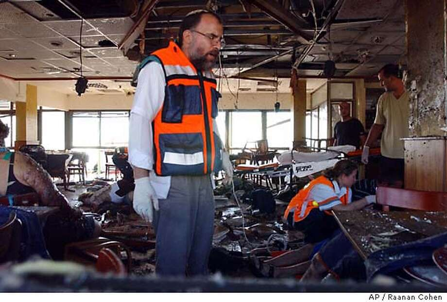 ** EDS NOTE: GRAPHIC CONTENT ** Rescue workers work inside the site of a suicide bombing in a restaurant in the northern Israeli city of Haifa Saturday Oct. 4, 2003. A Palestinian woman blew herself up in the Arab-owned Maxim beach restaurant Saturday, killing at least 19 people, including three children, and wounding about 40 in one of the deadliest attacks in the past three years. (AP Photo/ Raanan Cohen) ** ISRAEL OUT ** Photo: RAANAN COHEN