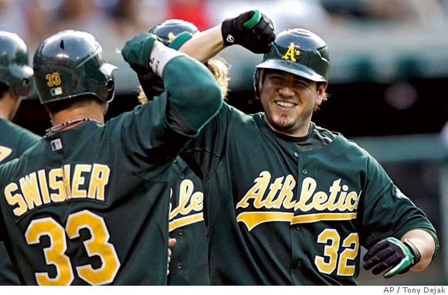 Oakland Athletics' Jack Cust (32) is congratulated by Nick Swisher after Cust hit a three-run homer off Cleveland Indians pitcher Fausto Carmona in the first inning of a baseball game, Wednesday, June 27, 2007, in Cleveland. (AP Photo/Tony Dejak) Photo: Tony Dejak