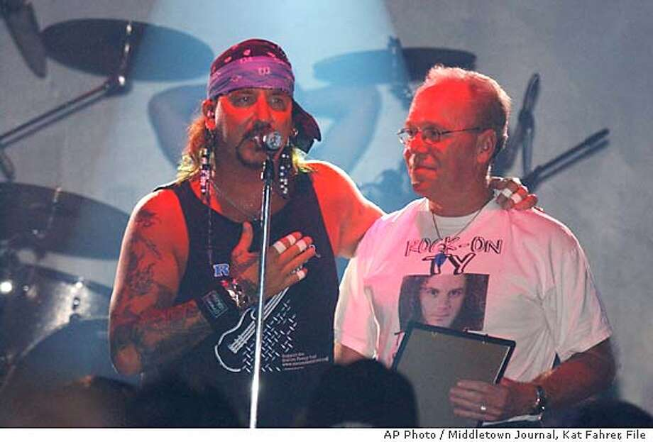 ** FILE ** Jack Russell, lead singer of Great White, introduces Pat Longley, father of Ty Longely, Great White guitarist who was killed in the fire Feb. 20, 2003, at The Station nightclub in West Warick, R.I., at the band's concert at C.C.'s Showcase in Middletown, Ohio, Sunday, Sept. 7, 2003. The concert's proceeds will go to The Station Family Fund, benefitting families of the fire's victims. (AP Photo / Middletown Journal, Kat Fahrer, File) Photo: KATHLEEN FAHRER