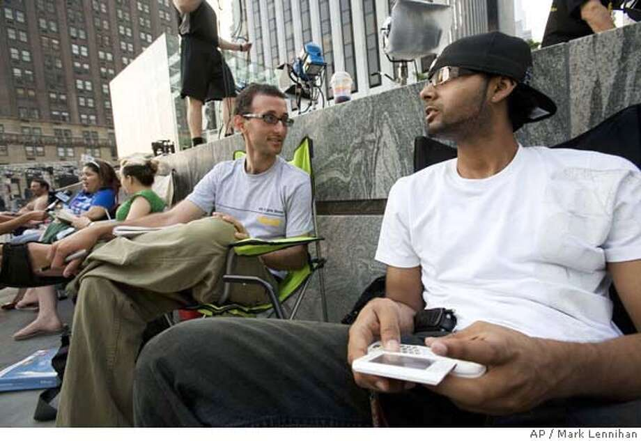 David Clayman, left, and Anthony Cardozo sit in line in front of an Apple store Wednesday, June 27, 2007 in New York. They are hoping to be some of the first people to buy the new Apple iPhone when it goes on sale Friday. (AP Photo/Mark Lennihan) Photo: Mark Lennihan