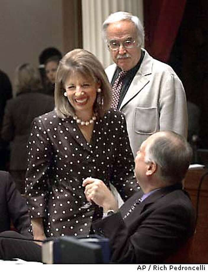 State Sen. Jackie Speier, D-Daly City, left, smiles while talking to state Sen. Sam Aanestad, R-Grass Valley, seated, after the employee health insurance bill she and State Sen. President Pro Tem John Burton, D-San Francisco, standing right, co-authored, was passed by the Senate at the Capitol in Sacramento, Calif., Friday, Sept. 12, 2003. The measure, which was approved 25-14, requires that companies with more than 200 employees begin offering health benefits by 2006, and smaller companies with 20 or more employees begin coverage in 2007. (AP Photo/Rich Pedroncelli) Photo: RICH PEDRONCELLI