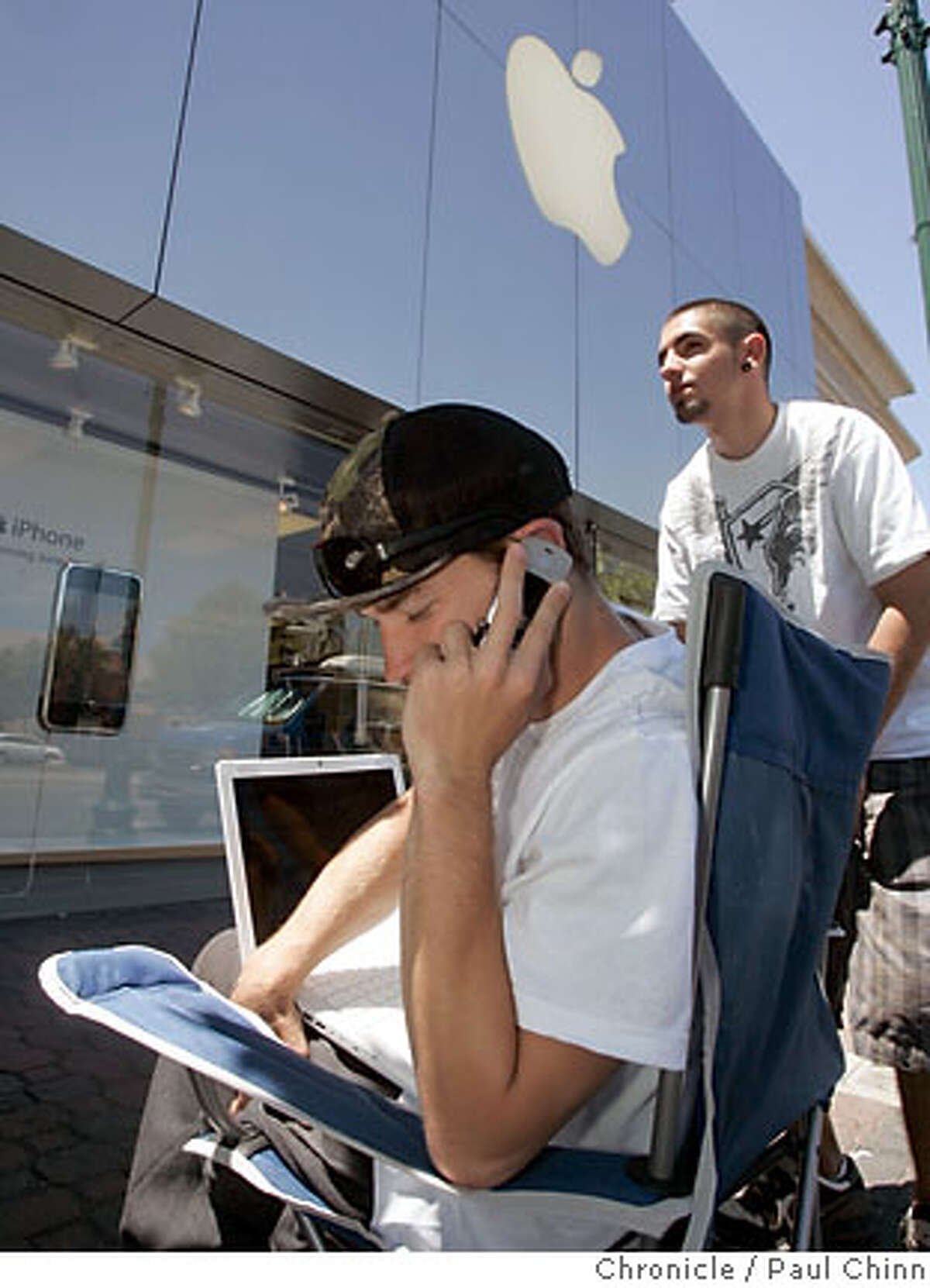 Josh May (on cellphone) and Nick Core were among four high school buddies from Benicia that were first in line to buy the highly anticipated iPhone in Walnut Creek, Calif. on Wednesday, June 27, 2007 when it goes on sale Friday at the Apple Store. The group hopes to sell the first two spots in line and then purchase up to five iPhones to sell on eBay and earn money for college. PAUL CHINN/The Chronicle **Josh May, Nick Core