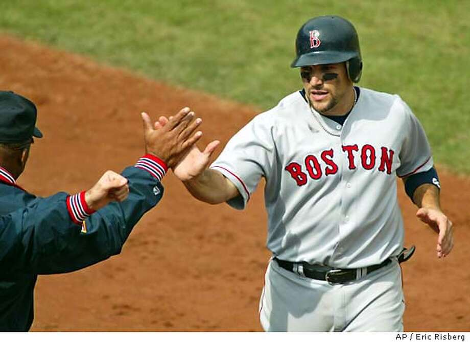 The Boston Red Sox' Doug Mirabelli high-fives in the dugout after scoring on a double hit by Johnny Damon in the third inning against the Oakland Athletics in game 2 of the American League Divisional Series playoff game, Thursday, Oct. 2, 2003, in Oakland, Calif. (AP Photo/Eric Risberg) Photo: ERIC RISBERG