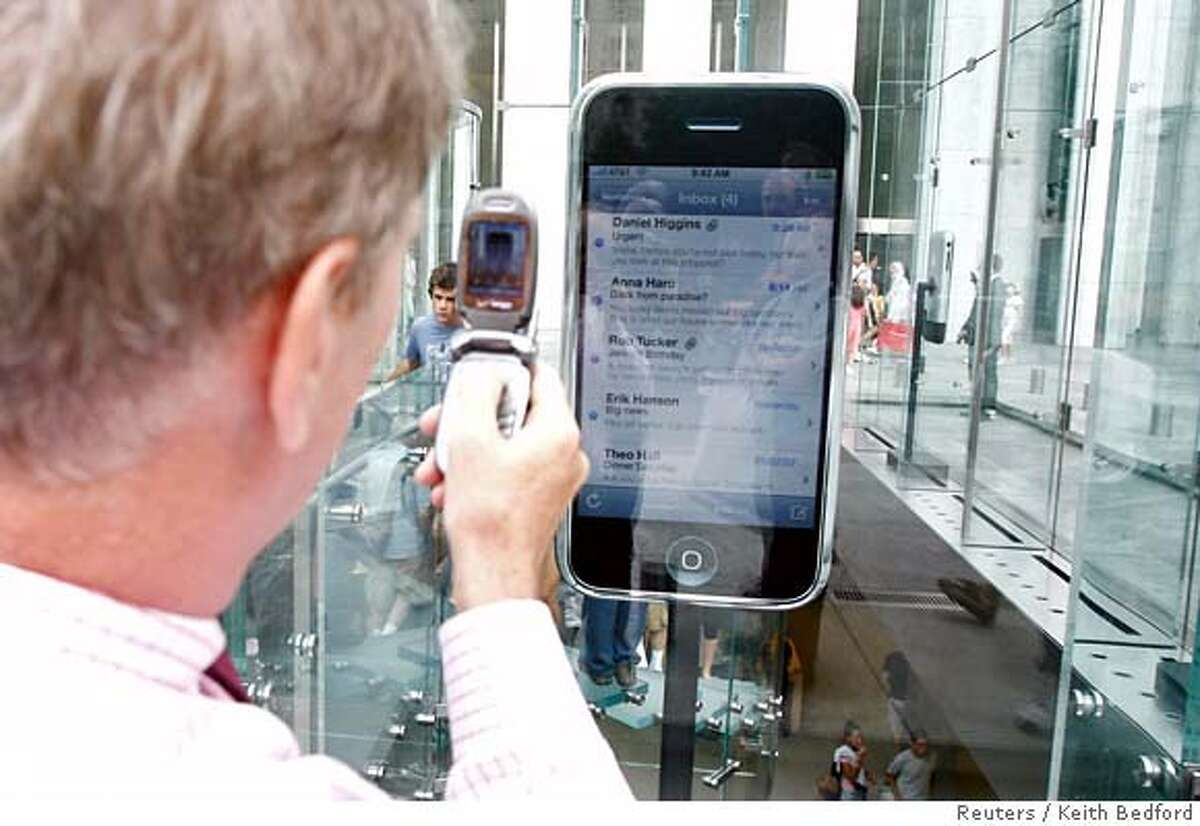 A passer-by takes a cell phone picture of a replica display of Apple's iPhone at the Fifth Avenue Apple store in New York, June 25, 2007. Apple's upcoming iPhone is shaping up as this year's must-have gadget, but several perceived shortcomings are pushing some potential buyers to wait for an updated version. REUTERS/Keith Bedford (UNITED STATES)