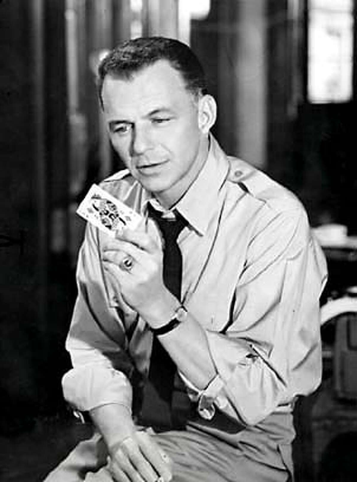 THIS IS A HANDOUT IMAGE. PLEASE VERIFY RIGHTS. Frank Sinatra contemplates the mystery-laden Queen of Diamonds in THE MANCHURIAN CANDIDATE.