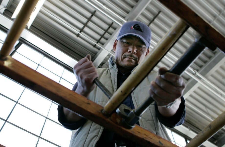 ladderxx_0008_df.jpg  Qing Du, is a pattern maker who repairs and builds ladders for the San Francisco Fire Department. San Francisco is one of the few cities that uses hand crafted wooden ladders for their fire department. Photographed in San Francisco on 6/19/07. Deanne Fitzmaurice / The Chronicle Mandatory credit for photographer and San Francisco Chronicle. No Sales/Magazines out. Photo: Deanne Fitzmaurice