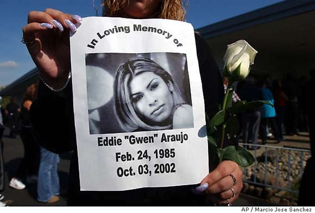 """** ADVANCE FOR WEEKEND EDITIONS, NOV 7-10 **FILE** Mayra Chavez holds a photo in memory of her friend, Eddie Araujo, during a wake in honor of Araujo at the Fremont Memorial Chapel in Fremont, Calif., Oct. 25, 2002. Last spring, when Newark Memorial High School's drama department decided to perform a play called """"The Laramie Project,"""" tragedy wasn't a word easily associated with Newark, Calif. But the student players were caught in a haunting coalescence of art and life when Araujo, a transgender teenfrom their own small suburb, was beaten and strangled to death. (AP Photo/Marcio Jose Sanchez)"""