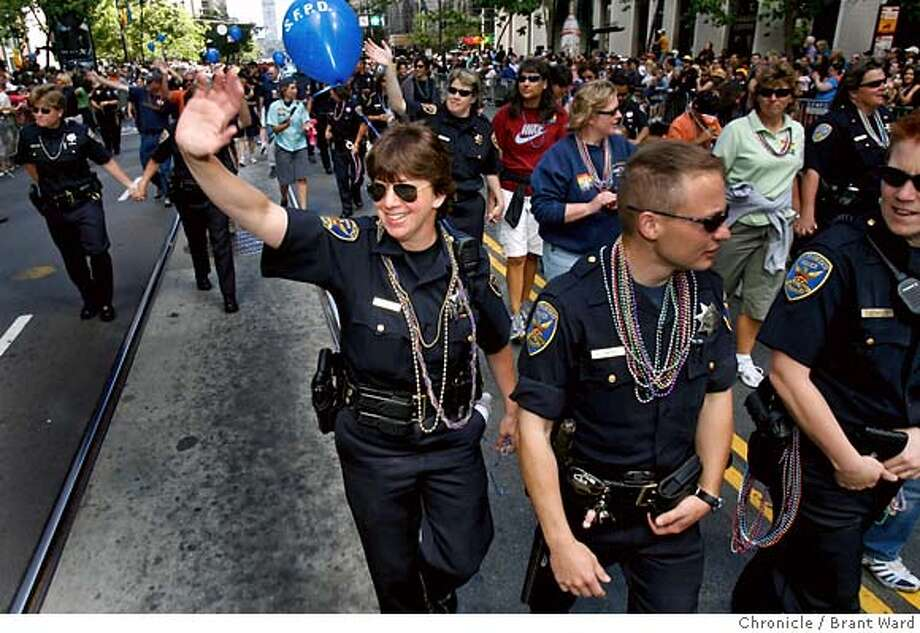 badge_pride_043.JPG  SFPD officer Lisa Frazer, center waving, marched with other LGBT members of the force and their supporters Sunday. She has marched in the parade for five years. {Brant Ward/San Francisco Chronicle}6/24/07 Photo: Brant Ward