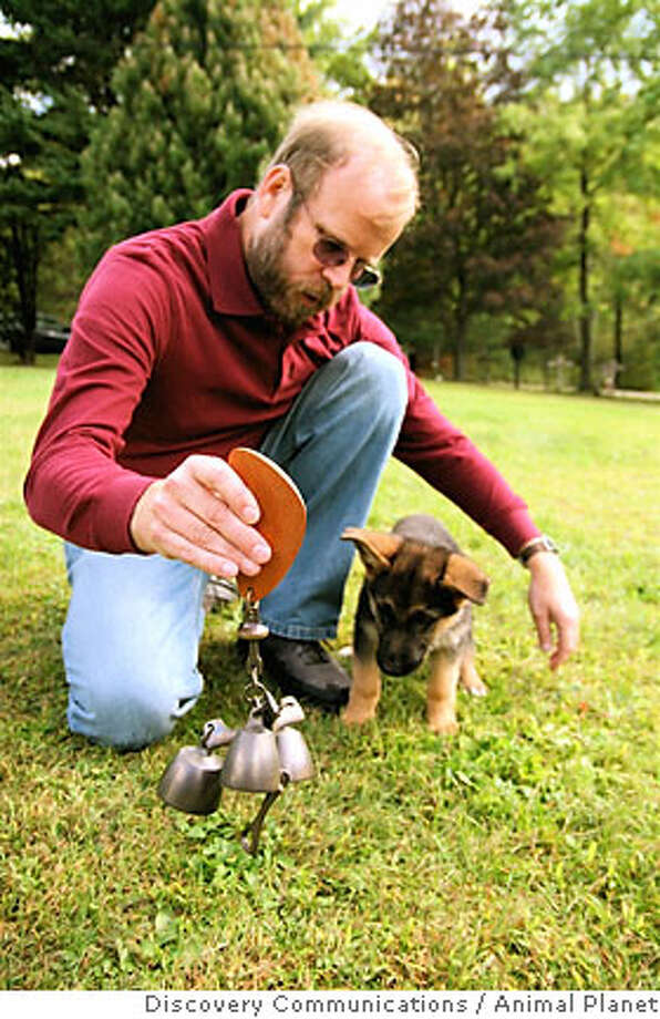 Brother Christopher with a New Skete puppy, doing early socialization  work, at the Monastery. Photo courtesy of Discovery Communications, Animal Planet