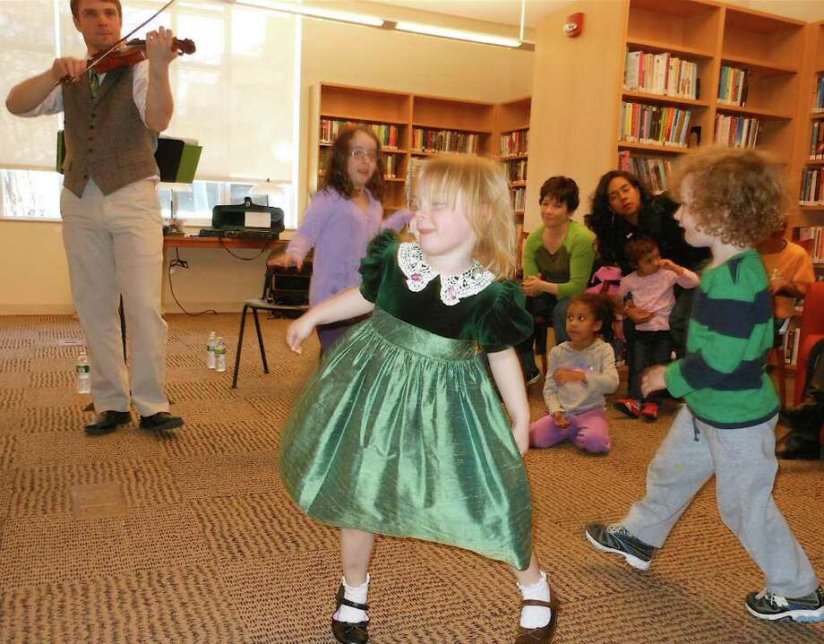 Children do a jig Saturday as Damian Connolly plays Irish music on a fiddle for St. Patrick's Day at the Fairfield Public Library. Photo: Mike Lauterborn / Fairfield Citizen contributed