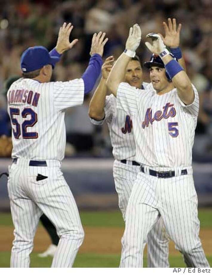 New York Mets' David Wright (5) is congratulated by coach Howard Johnson and Jose Valentin after he hit a game-winning single against the Oakland Athletics during the ninth inning of their baseball game, Saturday, June 23, 2007, at Shea Stadium in New York. The Mets defeated the Athletic,s 1-0. (AP Photo/Ed Betz) Photo: Ed Betz
