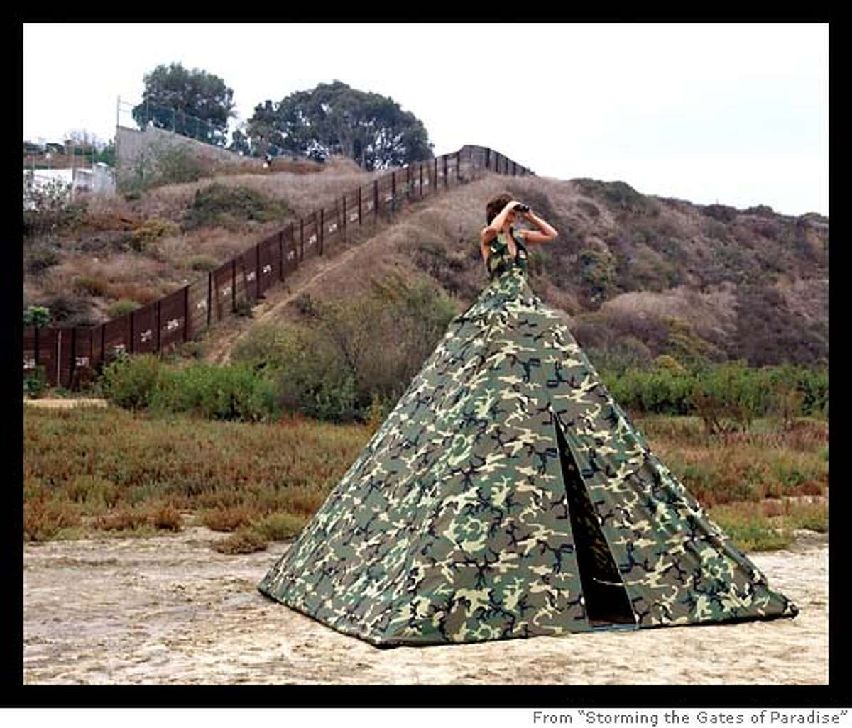 """This is a one time use to be used only with the review of Rebecca Solnit's book """"Landscapes For Politics."""" The following info must accompany the photo: Ms. Homeland Security - Illegal Entry Dress Tent by Robin Lasser Adrienne Pao (Installed beneath the California/Mexico border fence), 2005, 14�W x 14�D x 14�H. Gortex camouflage material, PVC pipes, and interior steel structure. Photograph: 50� W x 40� H Chromogenic Print. www.robinlasser.com www.adriennepao.com"""