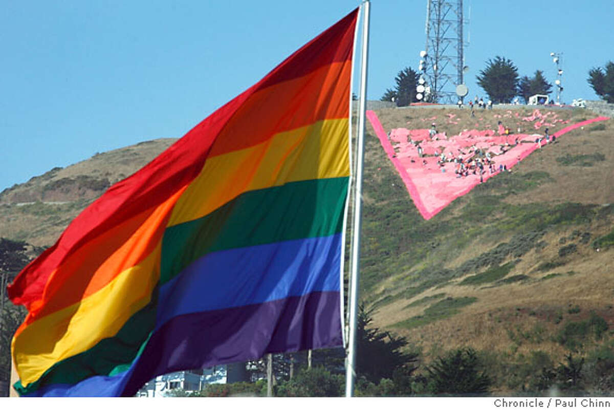 The rainbow flag at Market and Castro Streets flies below dozens of volunteers constructing a giant pink triangle on the slopes of Twin Peaks to celebrate Gay Pride weekend in San Francisco, Calif. on Saturday, June 23, 2007. The 200-foot wide symbol commemorates the history of the pink triangle which the Nazis forced gays to wear in concentration camps to identify them as homosexuals. PAUL CHINN/The Chronicle
