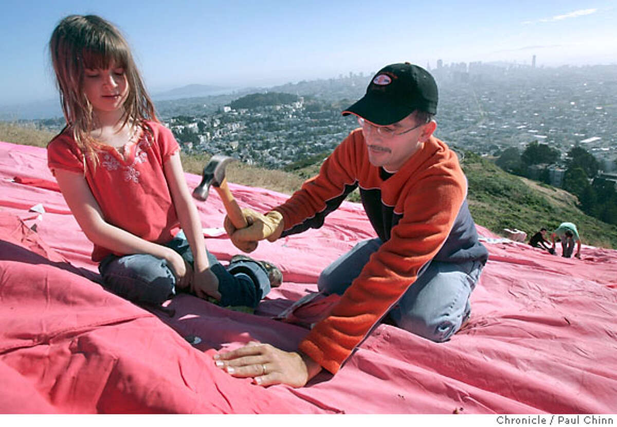 Joel Alegria (right) and his neighbor Leila Genschel-Kaylor, 8, attach a large fabric panel while joining dozens of volunteers that constructed a giant pink triangle on the slopes of Twin Peaks to celebrate Gay Pride weekend in San Francisco, Calif. on Saturday, June 23, 2007. The 200-foot wide symbol commemorates the history of the pink triangle which the Nazis forced gays to wear in concentration camps to identify them as homosexuals. PAUL CHINN/The Chronicle **Joel Alegria, Leila Genschel-Kaylor