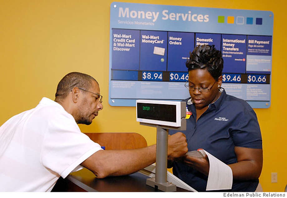 In this photo released by Edelman Public Relations, Wal-Mart employee Saketha Jarrett, right, helps Winston Stanford with a moneygram after a Money Center Grand Opening in Atlanta, Ga. Thursday, June 21, 2007. Wal-Mart, furthering a lucrative push to offer financial services to its customers, will sell prepaid Visa debit cards that would allow millions of low-income shoppers who don't have bank accounts to keep up with an increasingly cashless society. Wal-mart intends to have open 1,000 Money Centers by the end of 2008. (AP Photo/Edelman Public Relations, Barry Williams) Photo: Edelman Public Relations